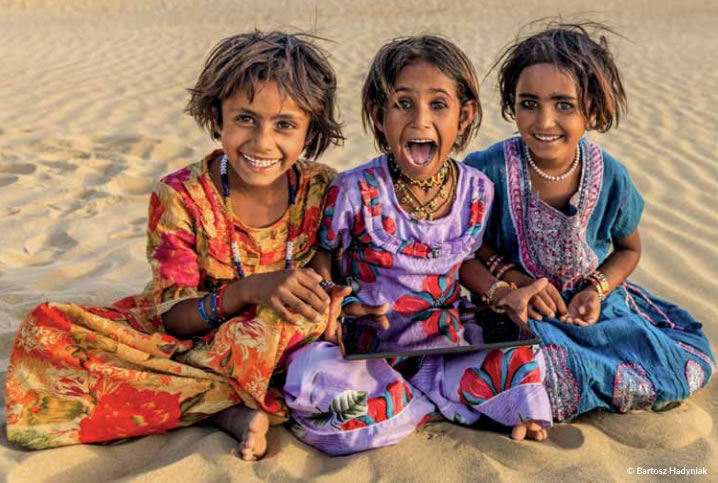 UNESCO - Three young girls in the Rajasthan Desert, India, share a tablet device.